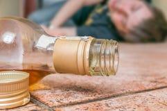 De alcoholische gedronken mens slaapt op vloer Fles met whisky vooraan royalty-vrije stock fotografie