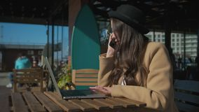 De alleen gelukkige vrouw rust in straatkoffie, typend op laptop, vraag door mobiel stock footage