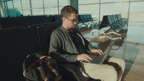 De alleen mannelijke passagier wacht zijn vlucht in een terminal en doorbladert in laptop