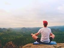 De alleen zittingsmens het praktizeren Yoga stelt op de rotsachtige piek Mens binnen nevelige morning do meditation royalty-vrije stock foto