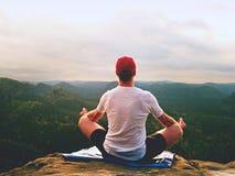 De alleen zittingsmens het praktizeren Yoga stelt op de rotsachtige piek Mens binnen nevelige morning do meditation royalty-vrije stock afbeelding