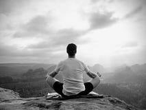 De alleen zittingsmens het praktizeren Yoga stelt op de rotsachtige piek Mens binnen nevelige morning do meditation stock fotografie