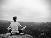 De alleen zittingsmens het praktizeren Yoga stelt op de rotsachtige piek Mens binnen nevelige morning do meditation royalty-vrije stock foto's