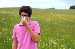 De allergische jongen met glazen en roze t-shirt blaast zijn neus royalty-vrije stock foto's