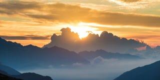 De Alpen bij zonsopgang De kleurrijke pieken van de hemel majestueuze berg, de valleien van de mistmist Zonnestraal en backlight  royalty-vrije stock afbeeldingen