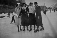 De ALPEN, ZWITSERLAND, 1932 - Vier glimlachende meisjes schaatsen op vakantie in de Zwitserse Alpen stock afbeeldingen