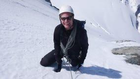 De alpinist hoog omhoog op een steil het noordengezicht in sneeuw en ijs kijkt omhooggaand en glimlacht stock afbeeldingen