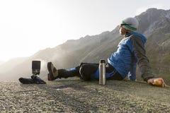 De alpinist maakt een onderbreking in de bergen en kookt thee stock foto's