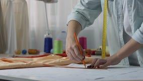 De amateur naaiende patronen van de kleermakerstekening thuis, aandacht aan details, hobby stock video