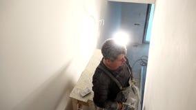 De amateurmens maalt muur Het manusje van alles richt muren op schuurpapier Handbediend stock video