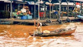 De Ambodianmensen levend op Tonle-Sapmeer in Siem oogsten, Kambodja Oude vrouw die een boot roeien Royalty-vrije Stock Foto