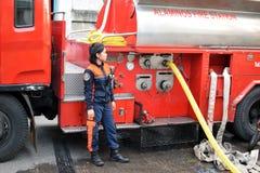De ambtenaar van de brandvrouw naast brandvrachtwagen tijdens huisbrand die binnenlandse barakhuizen uithaalde stock foto's