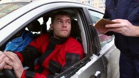 De ambtenaar van verkeerspolitie controleert de documenten van de bestuurder stock footage