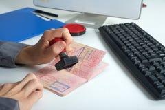 De ambtenaar zal in het paspoort stempelen Royalty-vrije Stock Afbeeldingen