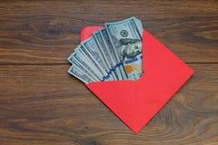 De Amerikaanse dollarbankbiljetten in de rode envelop op houten lijst, bonus, beloning, komt ten goede aan concept royalty-vrije stock afbeelding