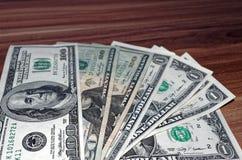 De Amerikaanse dollarbankbiljetten worden opgemaakt op houten achtergrond stock fotografie