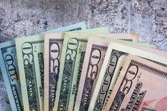 De Amerikaanse dollars uit op grijze leiachtergrond worden gewaaid, vlakte die lagen royalty-vrije stock afbeelding