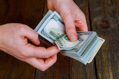 De Amerikaanse dollars in vrouwen overhandigt Stock Foto's