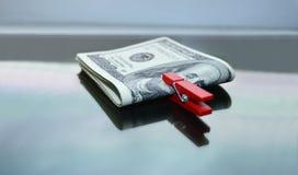 De Amerikaanse dollars worden vastgeklemd met een rode wasknijper Royalty-vrije Stock Afbeeldingen