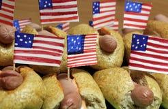 De Amerikaanse hotdogs met kleine Amerikaanse vlaggen sluiten plan, broodje en worst stock foto