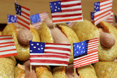 De Amerikaanse hotdogs met kleine Amerikaanse vlaggen sluiten plan, broodje en worst Royalty-vrije Stock Afbeelding