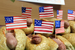 De Amerikaanse hotdogs met kleine Amerikaanse vlaggen sluiten plan, broodje en worst Stock Fotografie