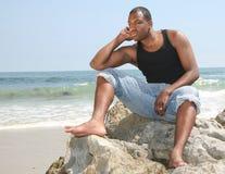 De Amerikaanse Jeugd in Diepe Gedachte op het Strand Royalty-vrije Stock Foto's