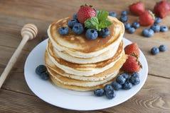 De Amerikaanse pannekoeken of fritters dienden met aardbei en bosbessenjam, heerlijk dessert voor ontbijt, rustieke stijl, houten stock foto's