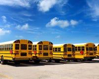 De Amerikaanse rij van de schoolbus onder blauwe hemel Stock Foto's