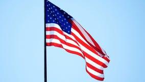 De Amerikaanse Vlag die van de V.S. of duidelijke blauwe hemel golven stock footage
