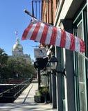 De Amerikaanse vlaggolven in de wind dichtbij het Stadhuis van Savanne, Georgië Stock Afbeelding