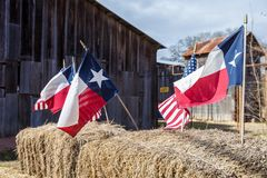 De amerikan- och Texas flaggorna som är ordnade på sugrörbaler, självständighetsdagengarnering arkivfoto