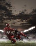 De amerikanska fotbollsspelarna i handling Arkivfoton