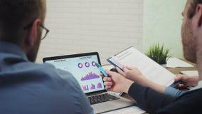 De analisten bij bureau werken bij laptop die statistieken tonen, bekijkend grafieken en grafieken stock videobeelden