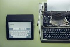 De analoge en digitale schrijfmachines liggen op de groene oppervlakte Continuïteit van generaties, technologische ontwikkelingco Stock Foto