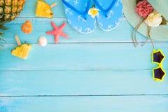 De ananasplakken, shells, de zeester, de pantoffels, de strohoed en de zonnebril op houten plankblauw kleuren stock afbeeldingen