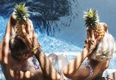 De ananassen van de paarholding boven hun hoofden Stock Fotografie