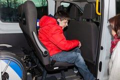 De Andicappedjongen wordt opgenomen door de schoolbus Royalty-vrije Stock Foto