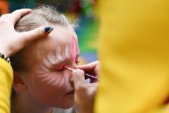 De animator trekt een meisje die op het gezicht bij een partij trekken stock afbeelding