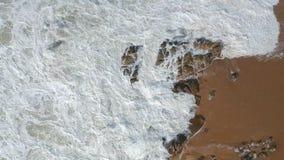De antenne schoot het vliegen van rechtstreeks omhoog het bekijken neer golven die op rotsen op zandig strand in Portugal verplet stock videobeelden