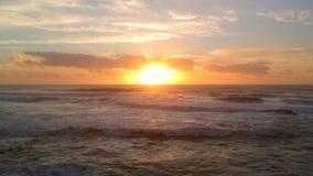 De antenne schoot over de Atlantische Oceaan bij zonsondergang, die langzaam zich vooruit over het breken van hieronder golven be stock video