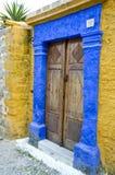 De antieke deuropening in Grieks eiland schilderde geel en blauw Stock Fotografie