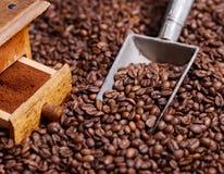 De antieke koffiemolen met grinded koffie in lepel op bonen stock afbeeldingen