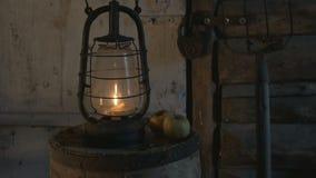 De antieke lamp met kaars op een houten lijst met appelen in de avond, de landbouwer bracht een lamp, een verlichte lantaarn, stock video