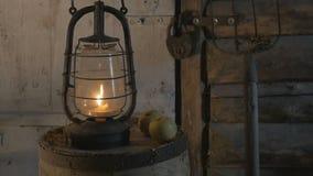 De antieke lamp met kaars op een houten lijst met appelen in de avond, de landbouwer bracht een lamp, een verlichte lantaarn, stock videobeelden