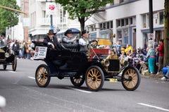 De antieke uitstekende oude doorwaadbare plaatsauto met mensen kleedde zich in historische kostuums die het berijden stock afbeeldingen