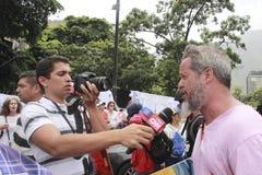 De antinicolas maduro-protesteerders wordt geïnterviewd tijdens een massieve demonstratie tegen dictatorshi stock afbeelding