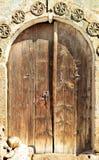 De antiquiteit overspande houten deuren met een steenpatroon en een metaalslot in het midden royalty-vrije stock foto