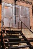 De antiquiteit roestte industriële deuren boven treden stock foto's