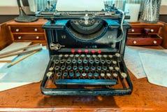 De antiquiteit, schrijfmachine met een blad van Witboek bevindt zich op een hout stock foto's